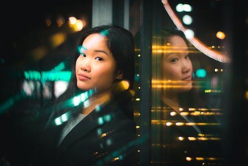 Portret Kobiety, Opierając Się Na Szklanej ścianie