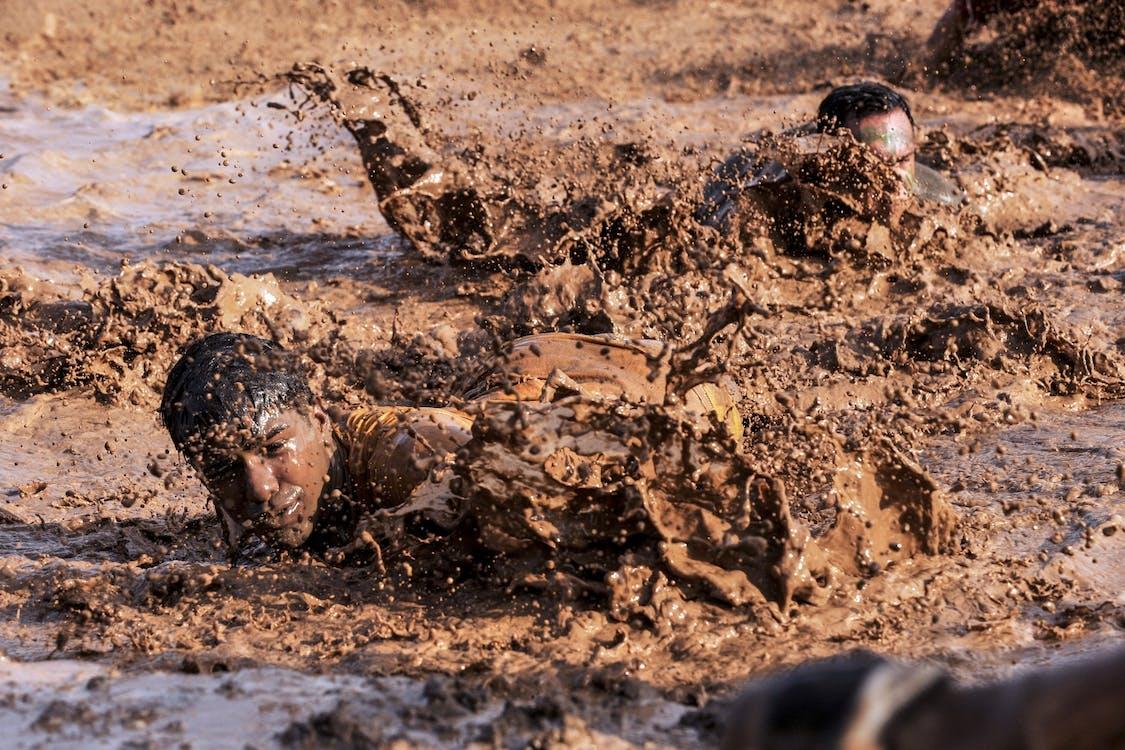 Two Men Crawling on Mud