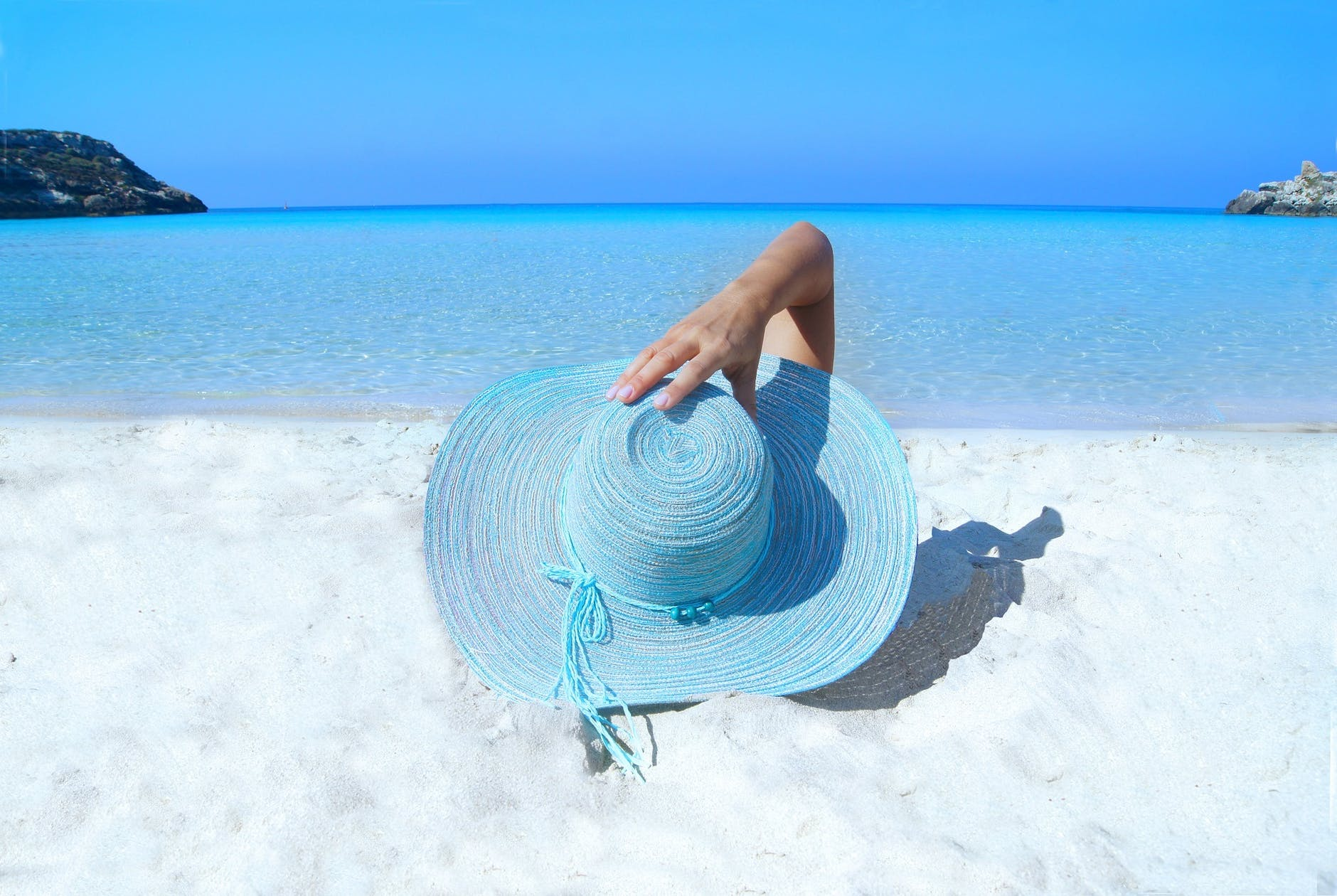 Pessoa de costas deitada na praia no verão com chapéu