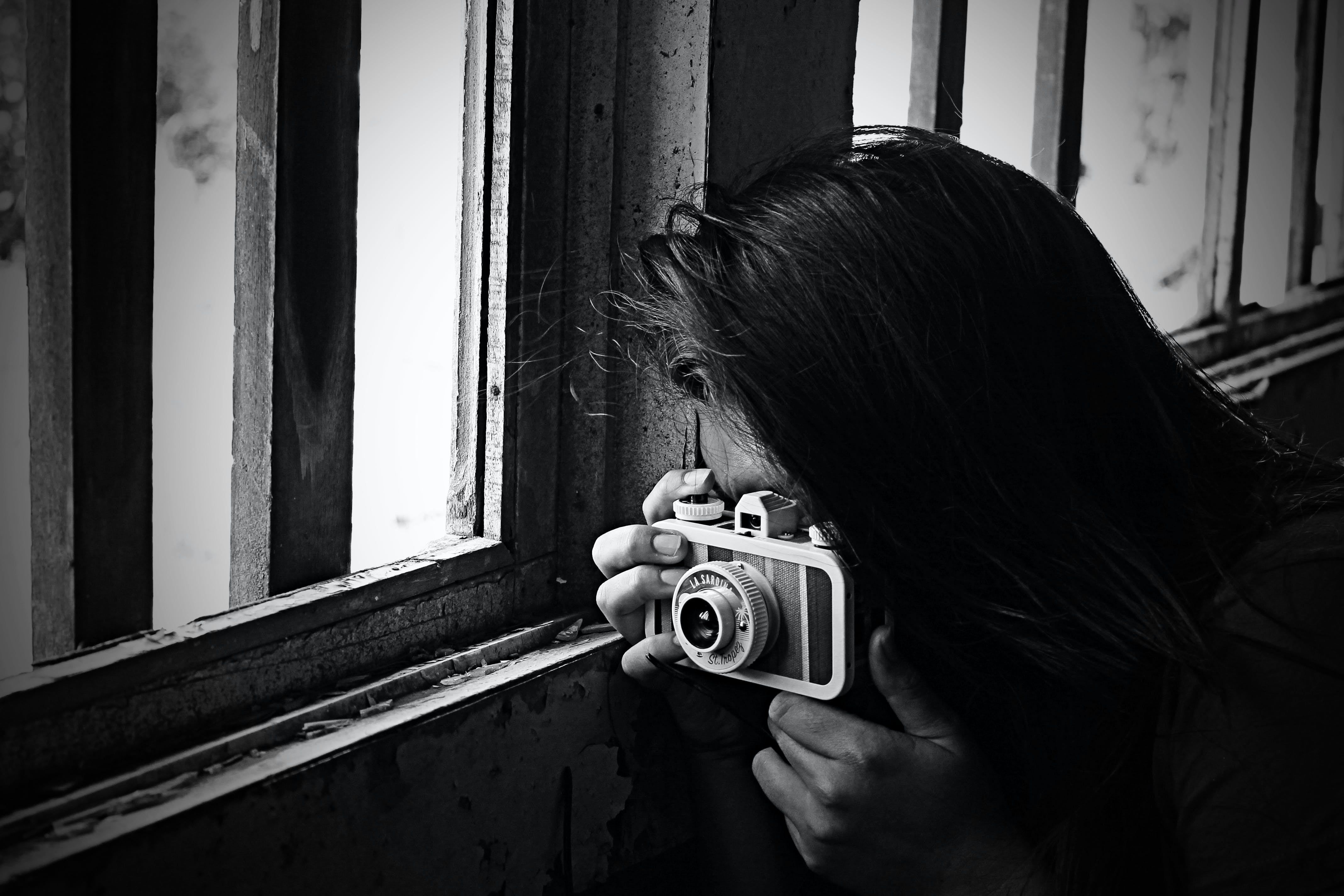 Grayscale Photo of Woman Taking Photo Beside Window