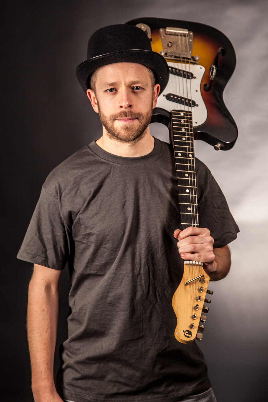 Man in Black T Shirt Holding Electric Guitar Upside Down