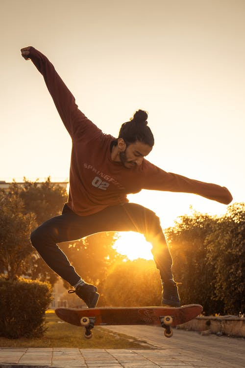Sun Rays Coming Through Man Wearing Red Crew-neck Long-sleeved Shirt Skateboard