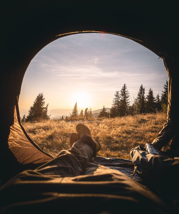 Person Lying Inside the Tent Through the Grass Field Under the Golden Hour