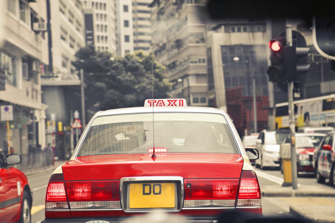 Red and White Taxi on Road