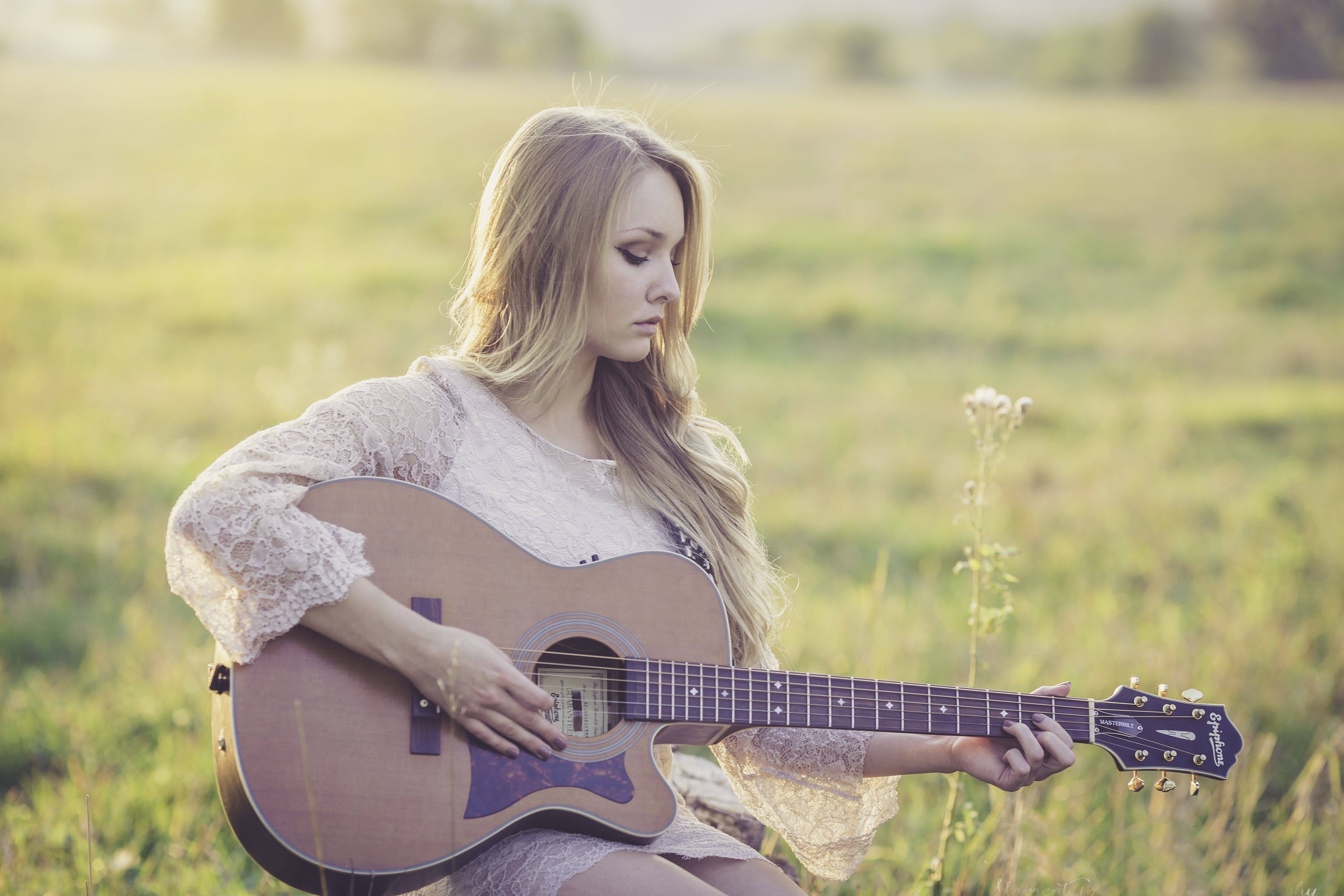Woman Playing Brown Wooden Acoustic Guitar during Daytime