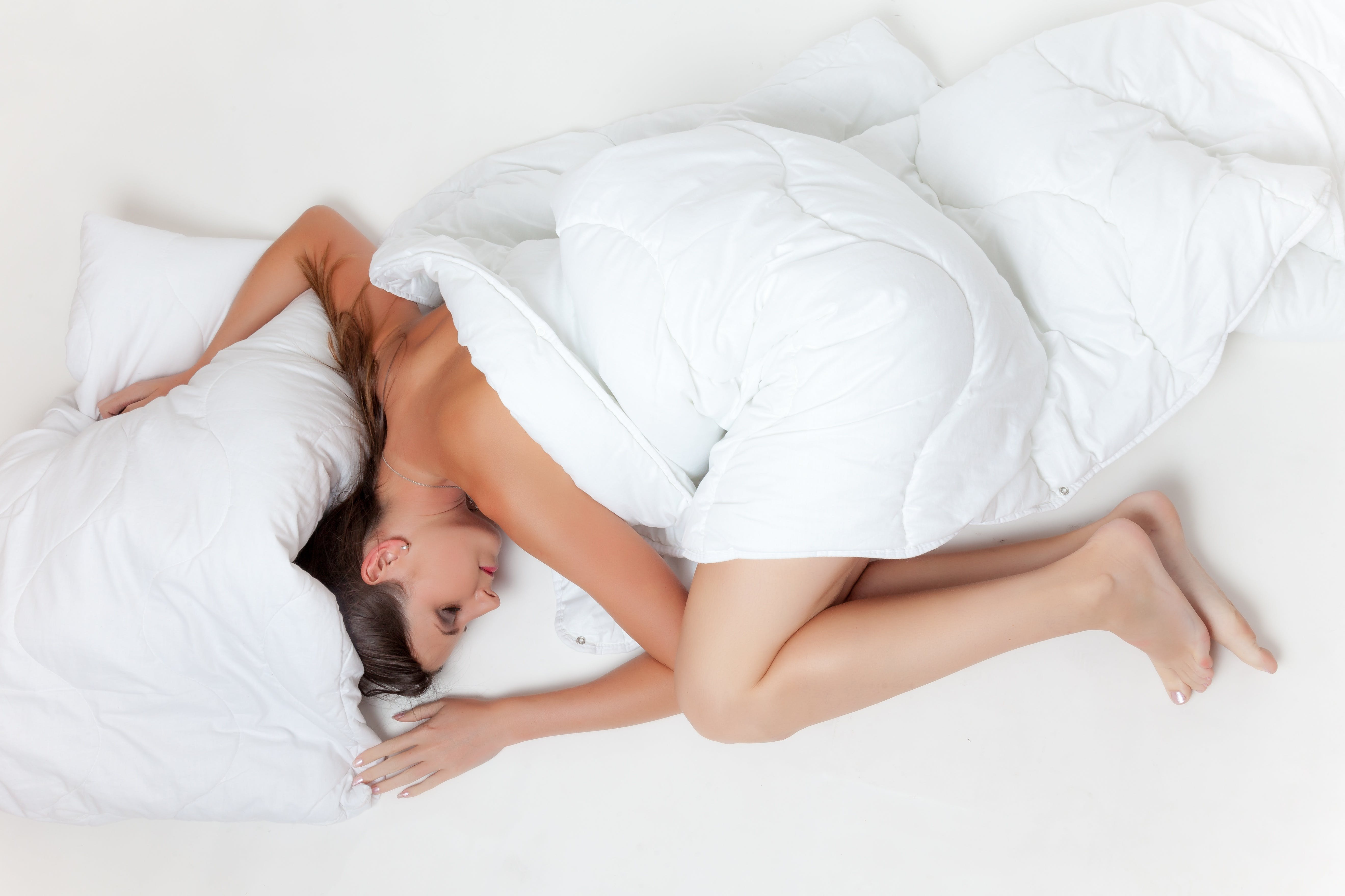 Woman Lying on White Textile Touching White Pillow
