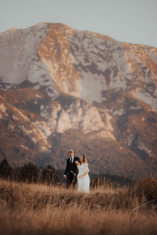 Groom and Wife Standing Near Mountain