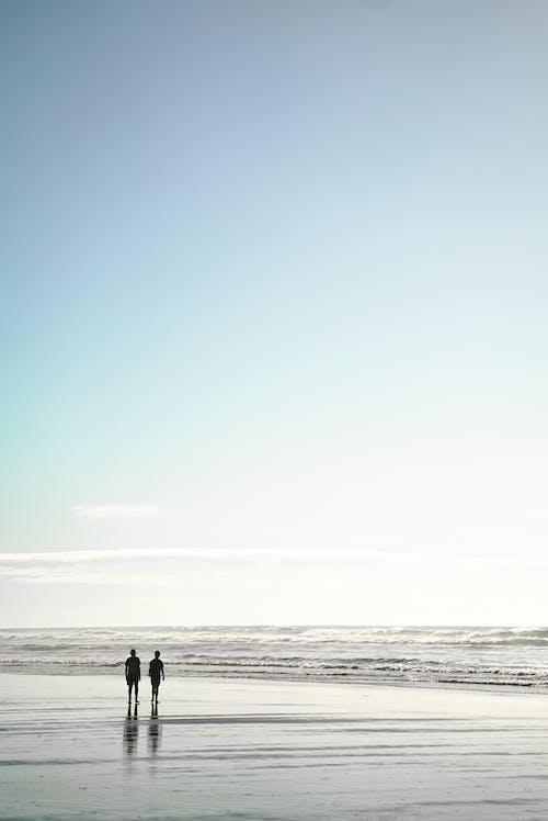 Two People Standing on Seashore