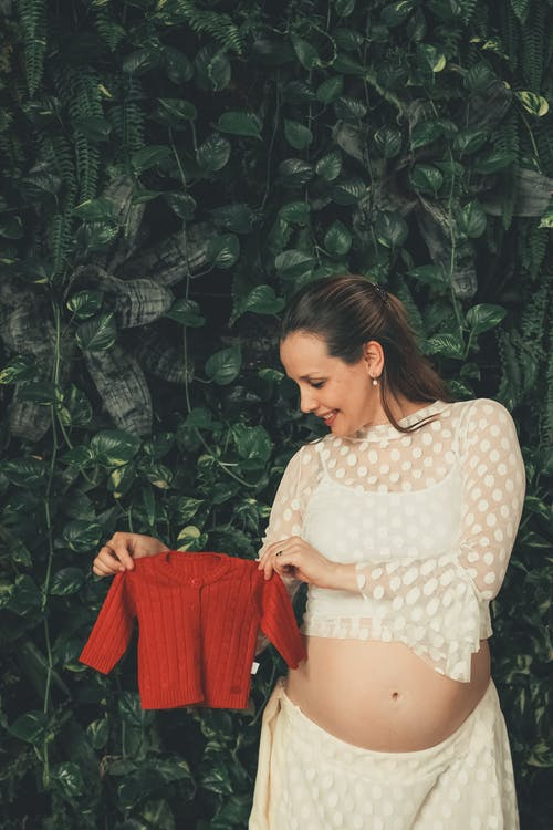 Happy pregnant woman with red baby shirt