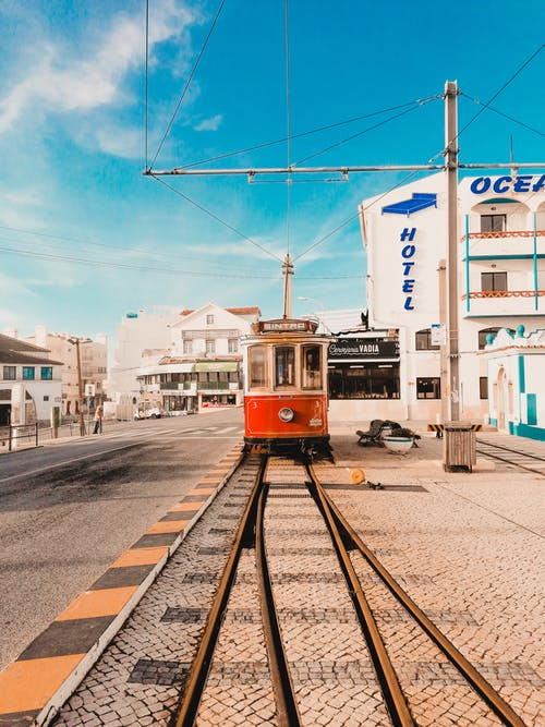 Red and White Tram Near Ocean Hotel Under Blue and White Sky