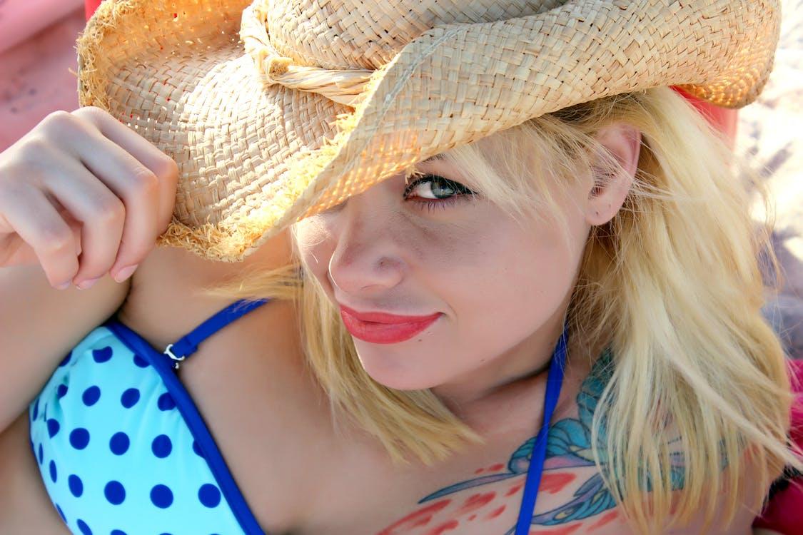Woman in Teal Bikini Holding Straw Hat