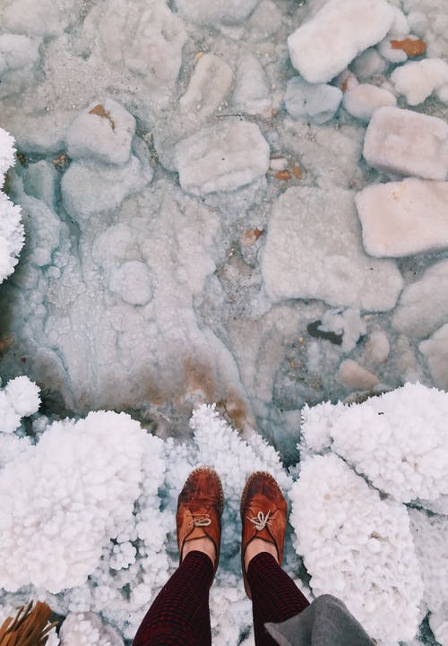 From above of crop anonymous female traveler in boots standing on rough surface covered by crystalline sea salt