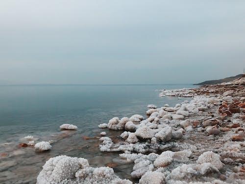 Crystalline salt formations on seashore under overcast sky