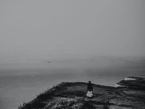 Grayscale Photography of Person on Cliff