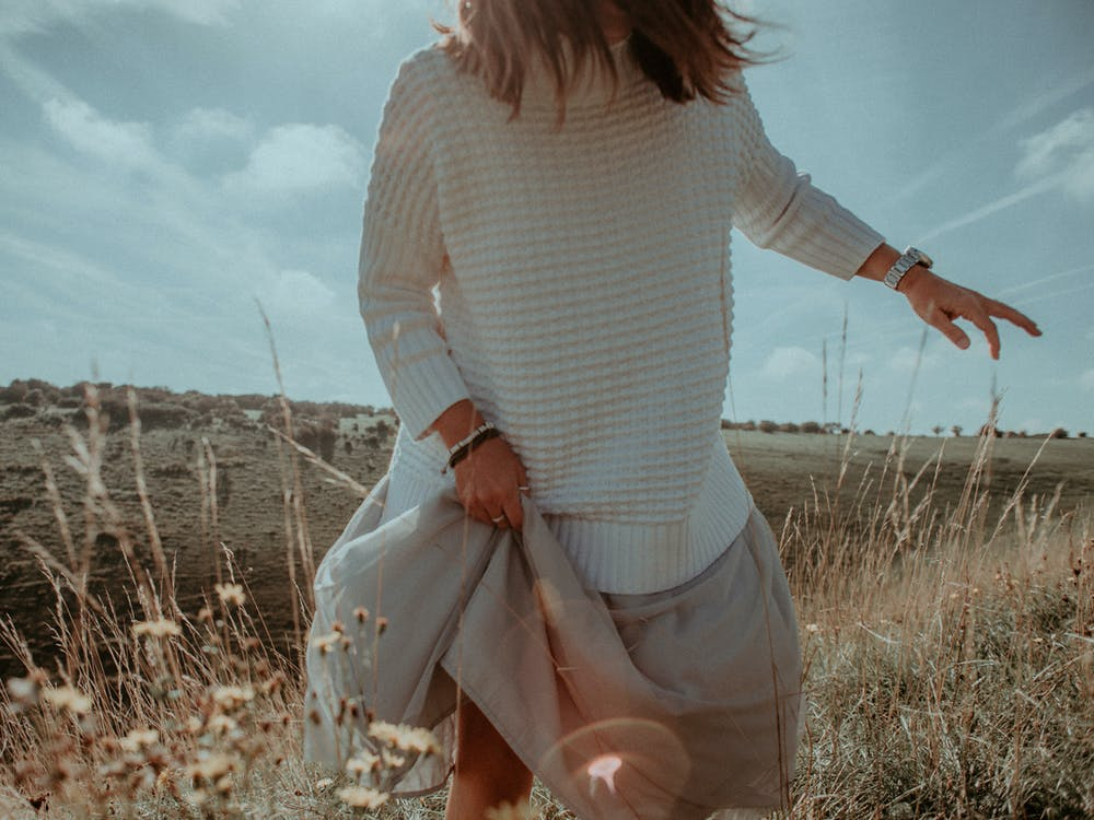 Standing Woman in White Sweater on Plant Field
