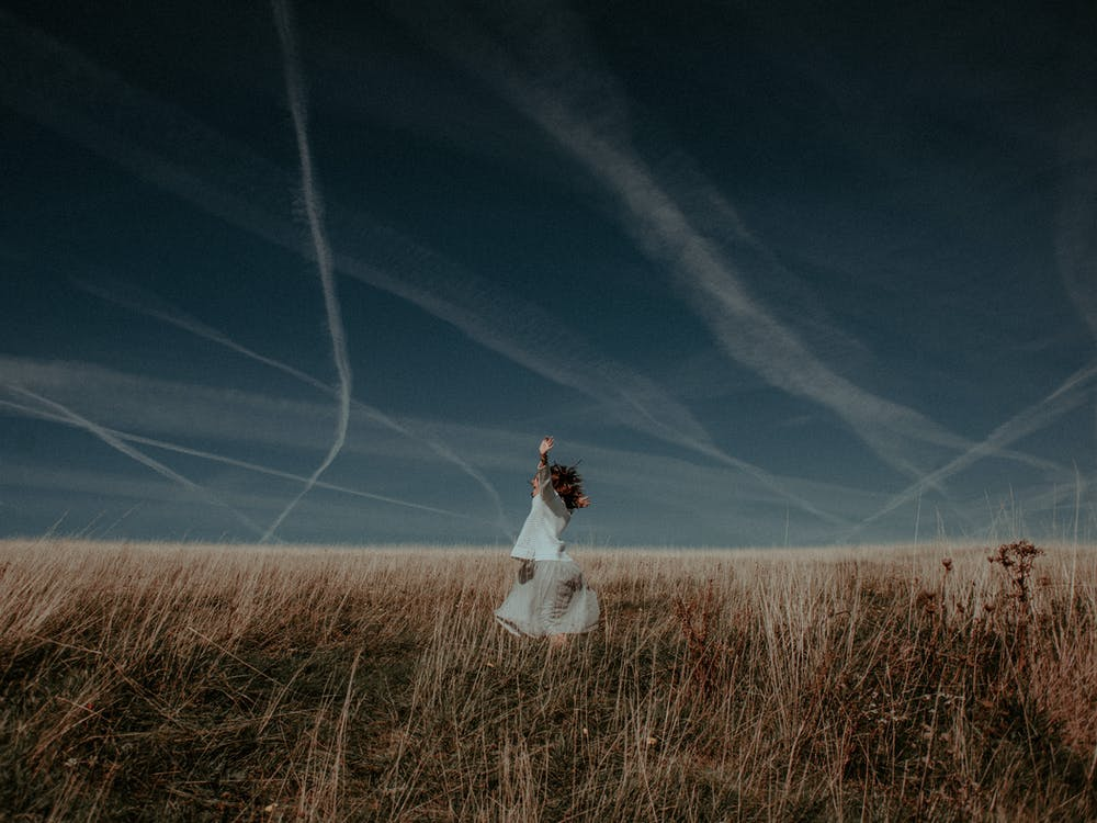 Woman in White Dress Standing on Plant Field