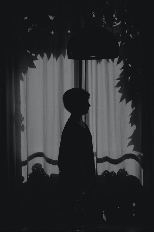 Silhouette of Person in Front of Curtains