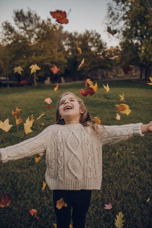 Девушка в вязаном свитере стоит снаружи с падающими листьями