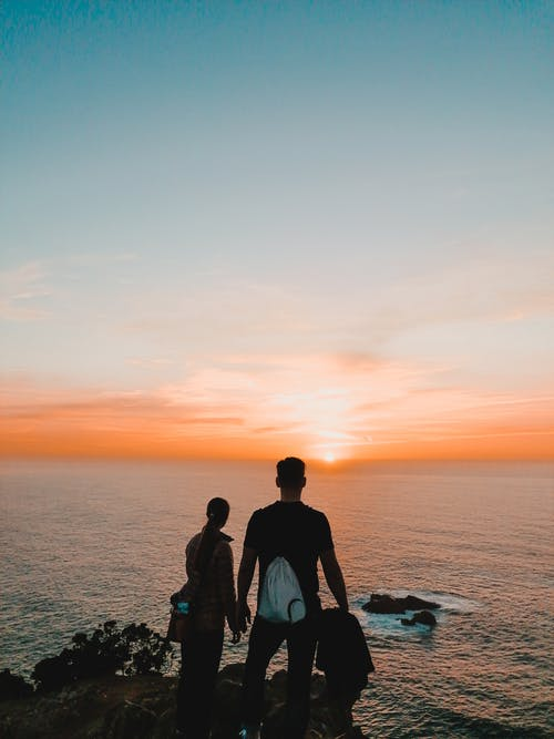 Couple Standing in Front of Sea during Golden Hour