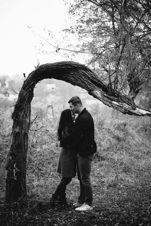 Grayscale Photography of Man Kissing Forehead of Woman Standing Near Tree