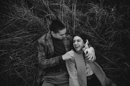 Grayscale Photography of Couple on Plant Field