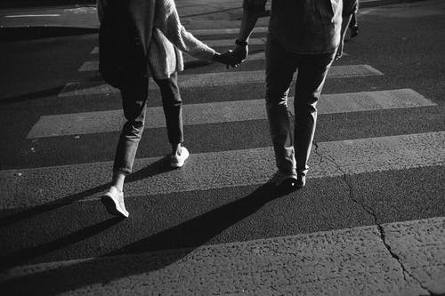 Greyscale Photo of Couple Walking Across the Road