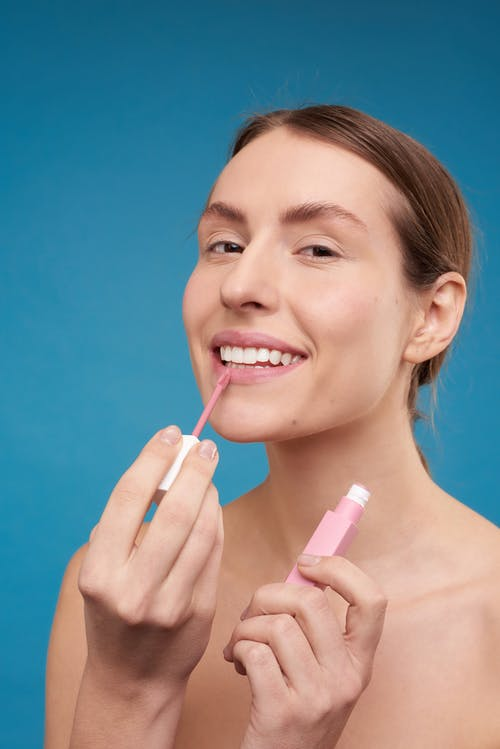 Woman Putting on Pink Lipstick