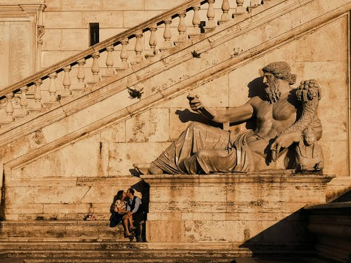 Photo Of Couple Kissing Beside Statue