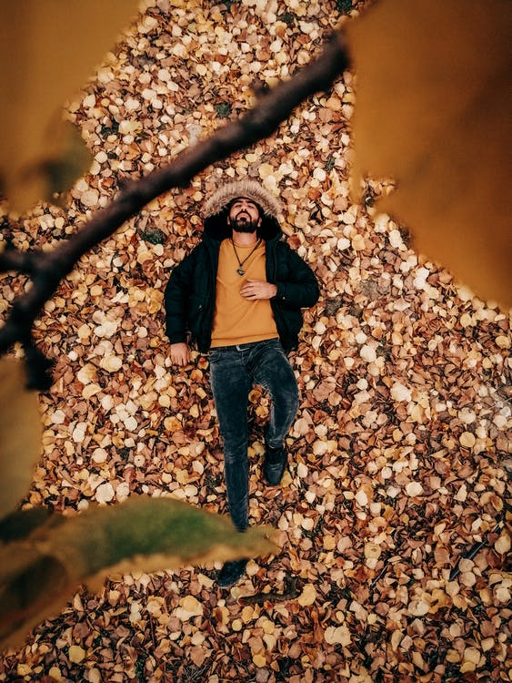 Photo Of Man Laying On Dried Leaves