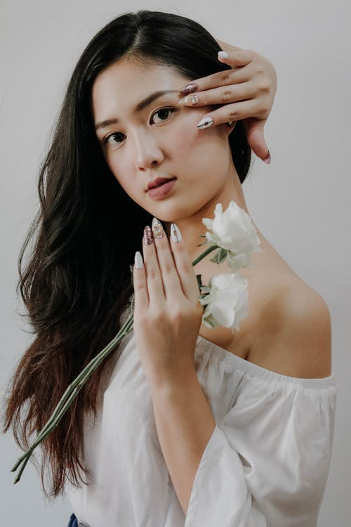Woman Wearing White Off-shoulder Blouse Holding White Rose Flower While Touching Her Hair