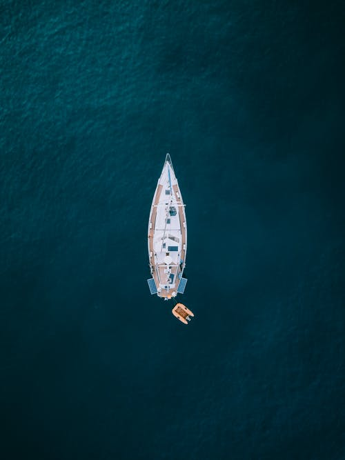 Aerial Photography of White and Brown Boat on Body of Water