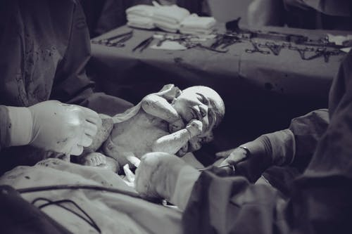 Grayscale Photography of Unknown Person Carrying Newborn Baby