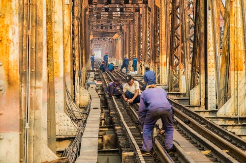 Group of anonymous male technicians in dirty uniforms building railroad together in city