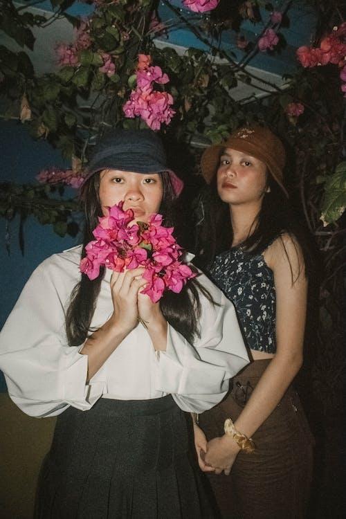 Two Women Standing Near Pink Bougainvillea Flowers