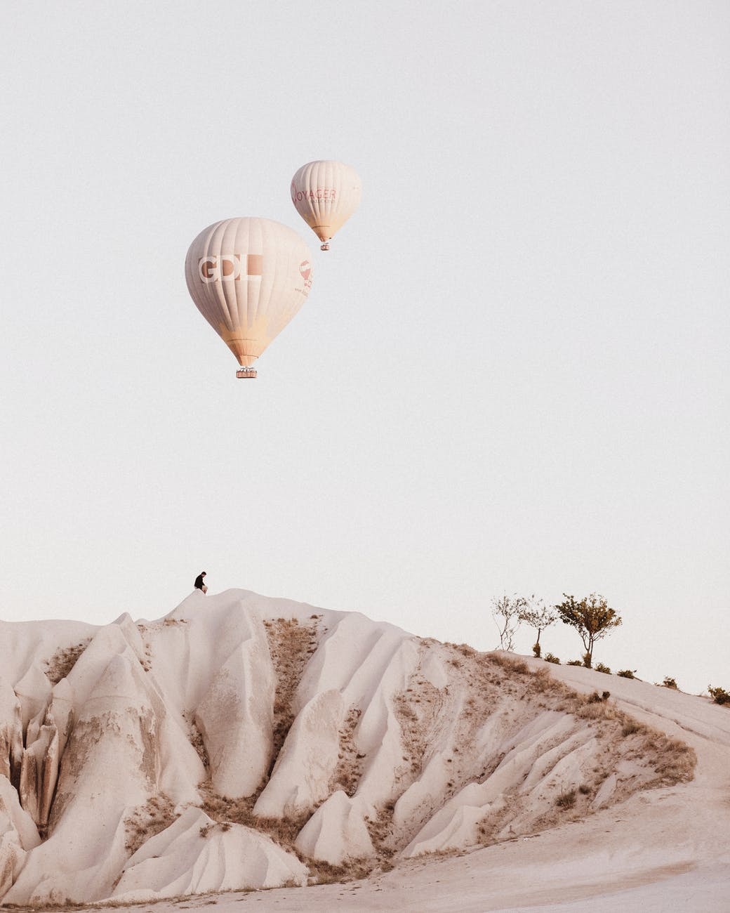 Peaceful image of hot air balloons drifting over the desert in Turkey.