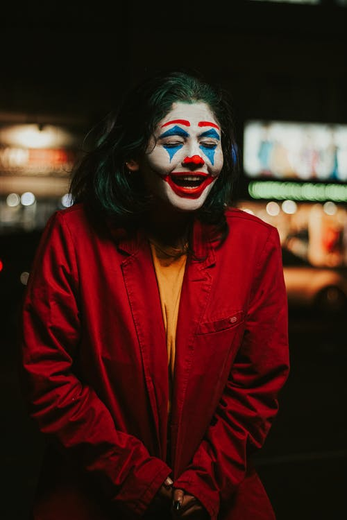 Shallow Focus Photo of Person in Red Coat With Clown Face Paint