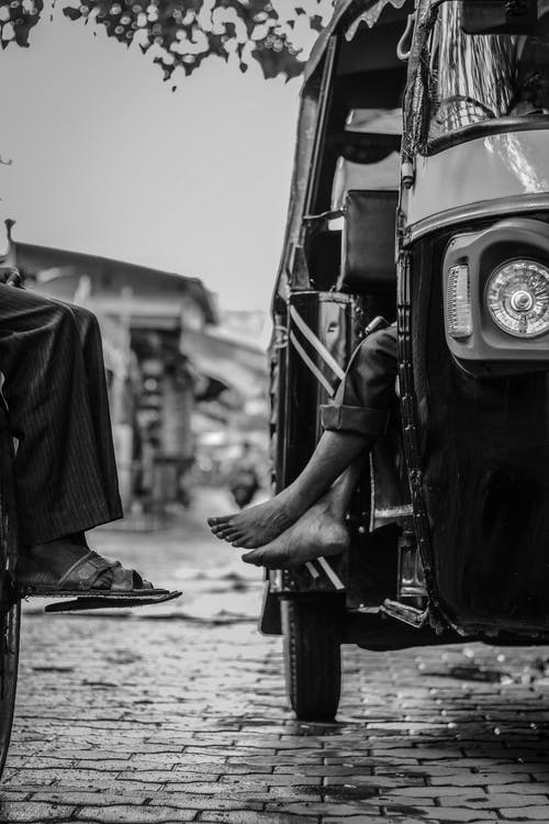 Grayscale Photography of Person Sitting Inside Tuk-tuk