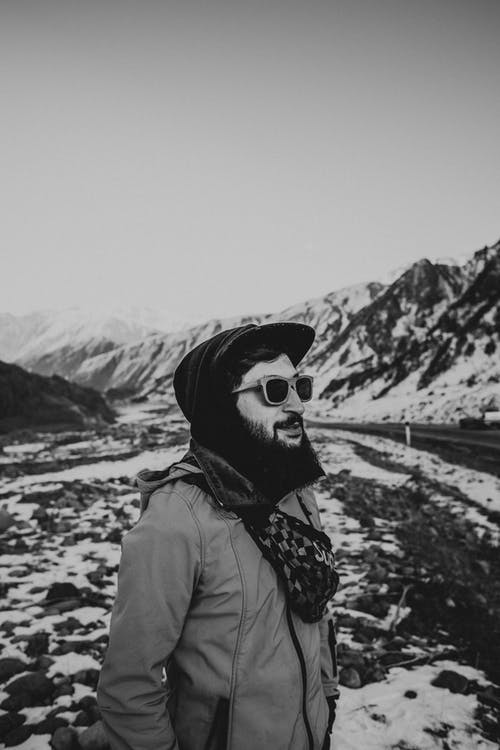 Man in Beige Jacket and Fitted Cap by Snow Covered Mountains