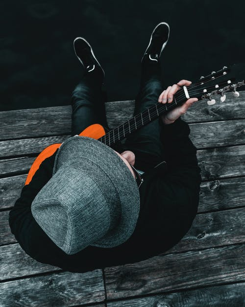 Person Wearing Gray Fedora Hat Playing Acoustic Guitar