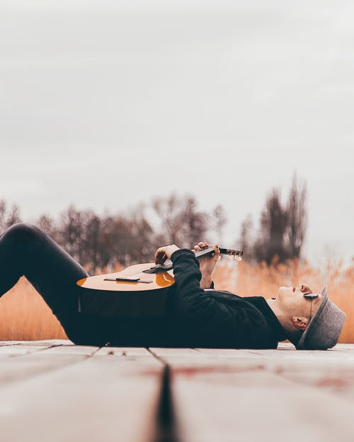 Man With Guitar Lying on Dock
