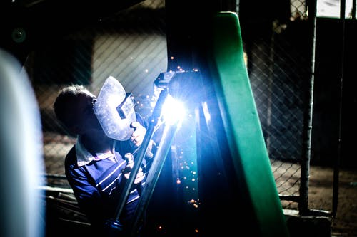Industry worker welding iron pieces at night