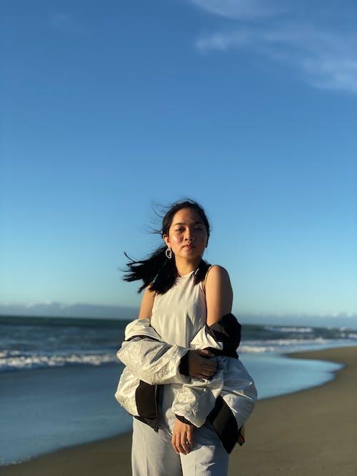 Woman in White Sleeveless Dress Standing on Beach