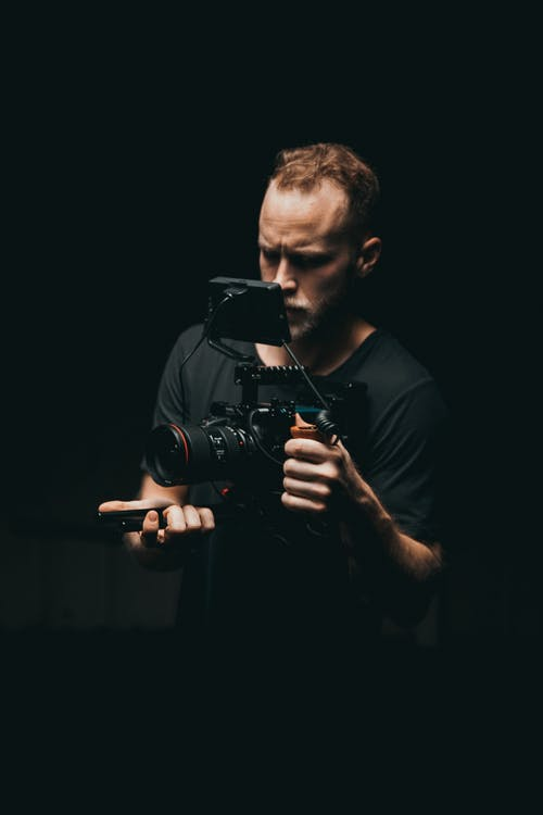 Shallow Focus Photo of Man Wearing Black Dslr Camera