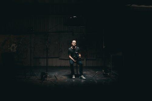 Selektive Fokusfotografie Des Sitzenden Mannes Auf Gedimmtem Beleuchtetem Raum