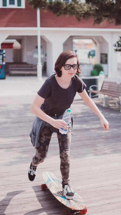 Woman Holding Water Bottle Skateboarding