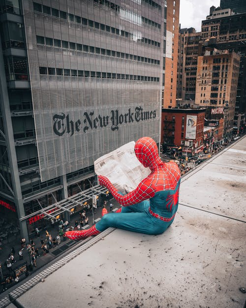 Spiderman Reading Newspaper on Top of Building