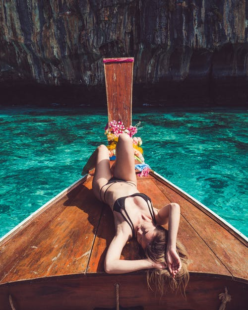 Peaceful young woman sunbathing lying on traditional boat floating in sea