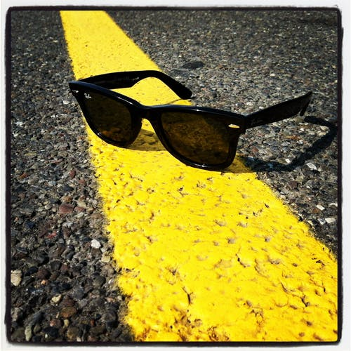 Black Ray-ban Wayfarer Sunglasses over Yellow Line on Street