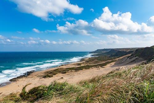 Amazing view of sandy seashore near foamy blue sea beneath clear blue sky