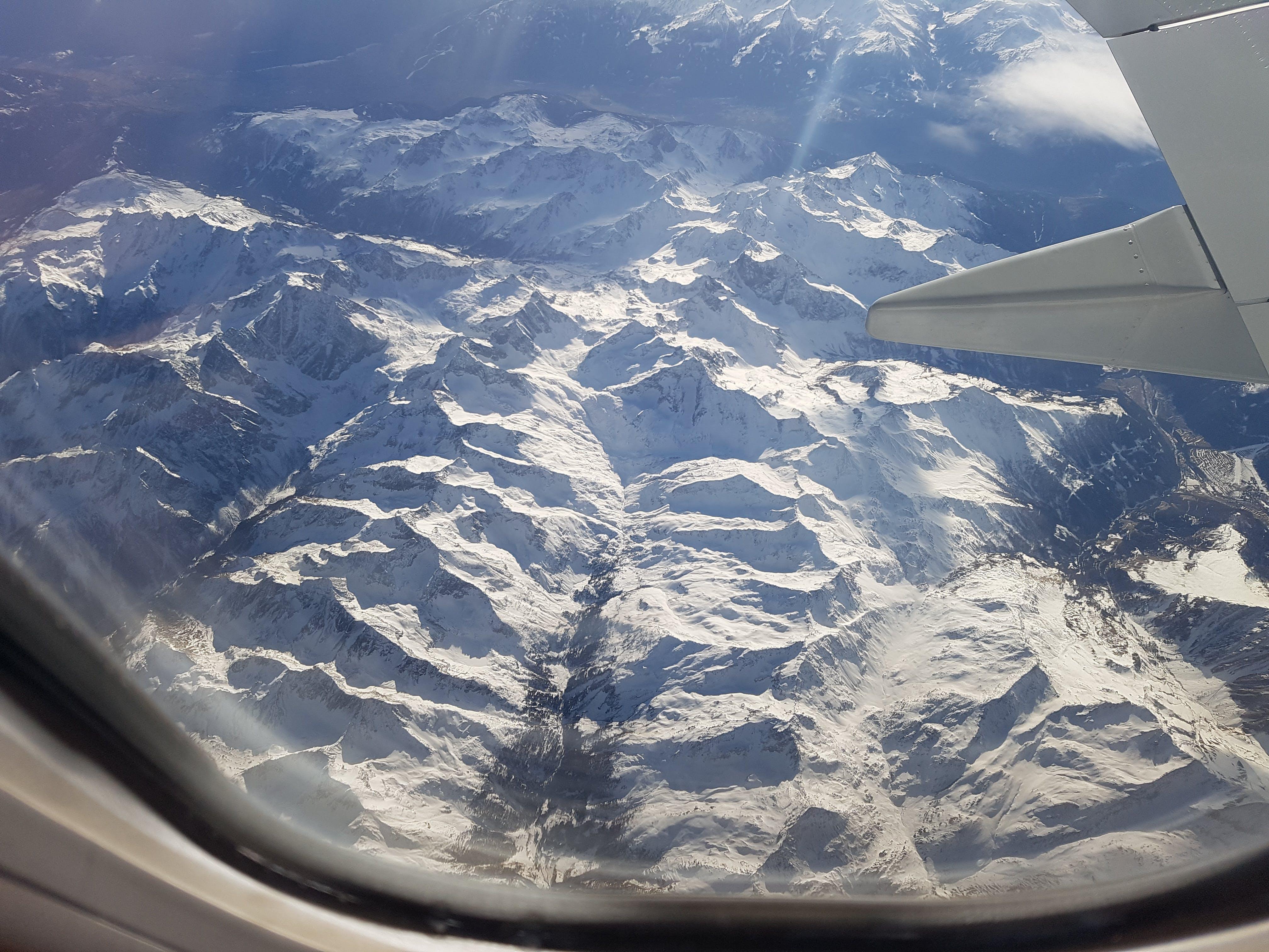 Free stock photo of on airplane above mountains snow